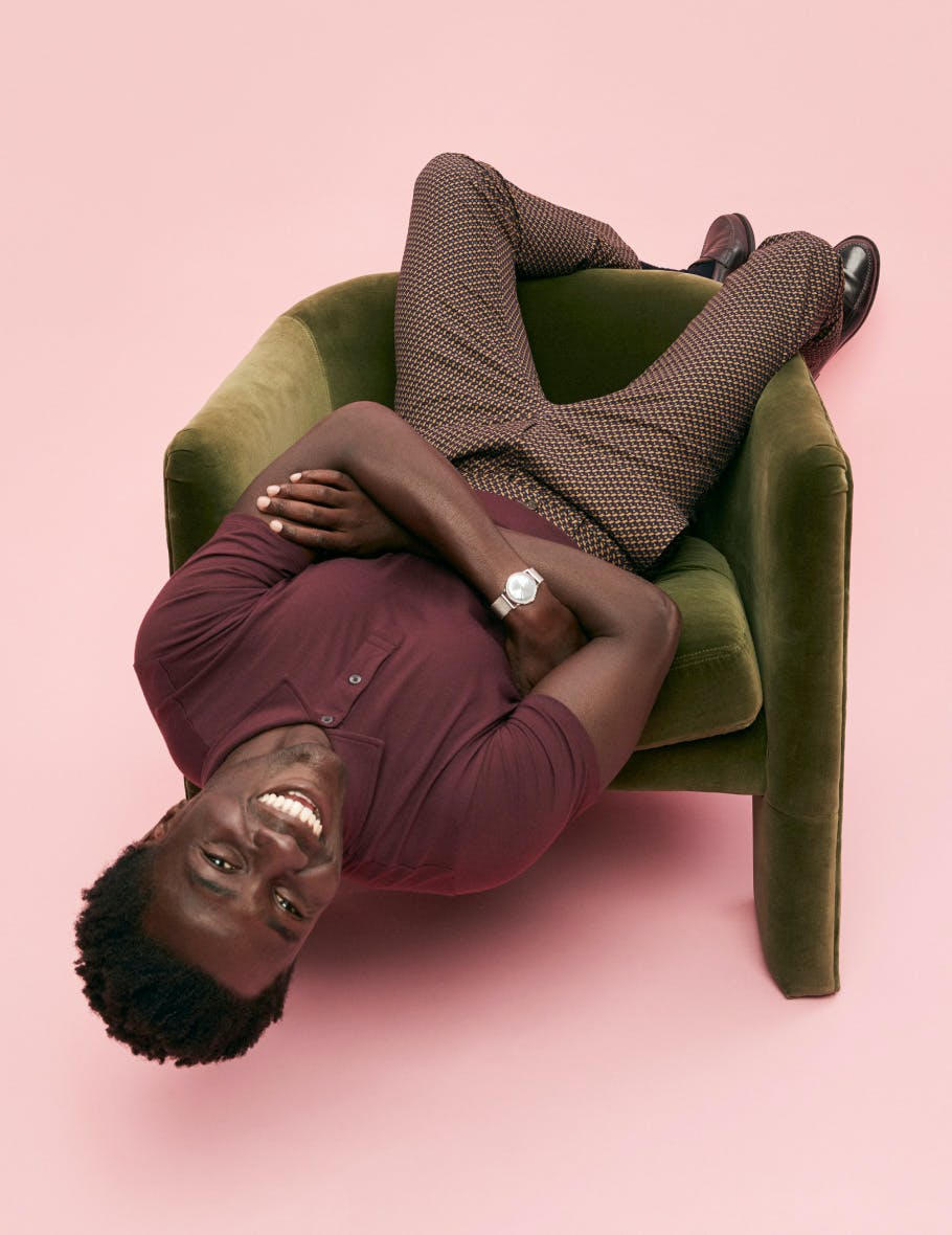 Man wearing a burgundy polo sitting up side down in a chair
