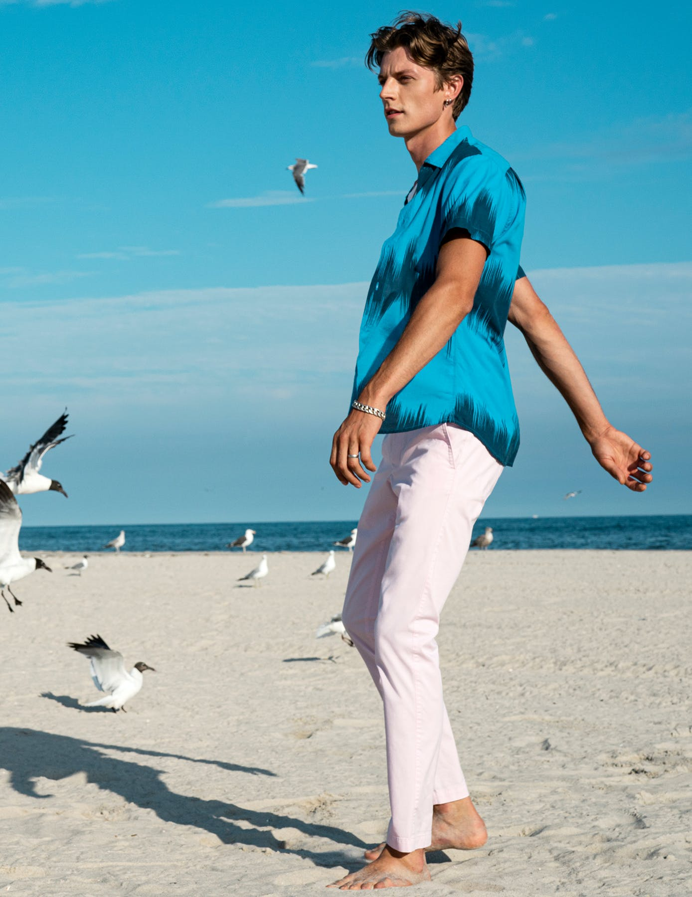 Man on the beach wearing blue Riviera Shirt and pink pants