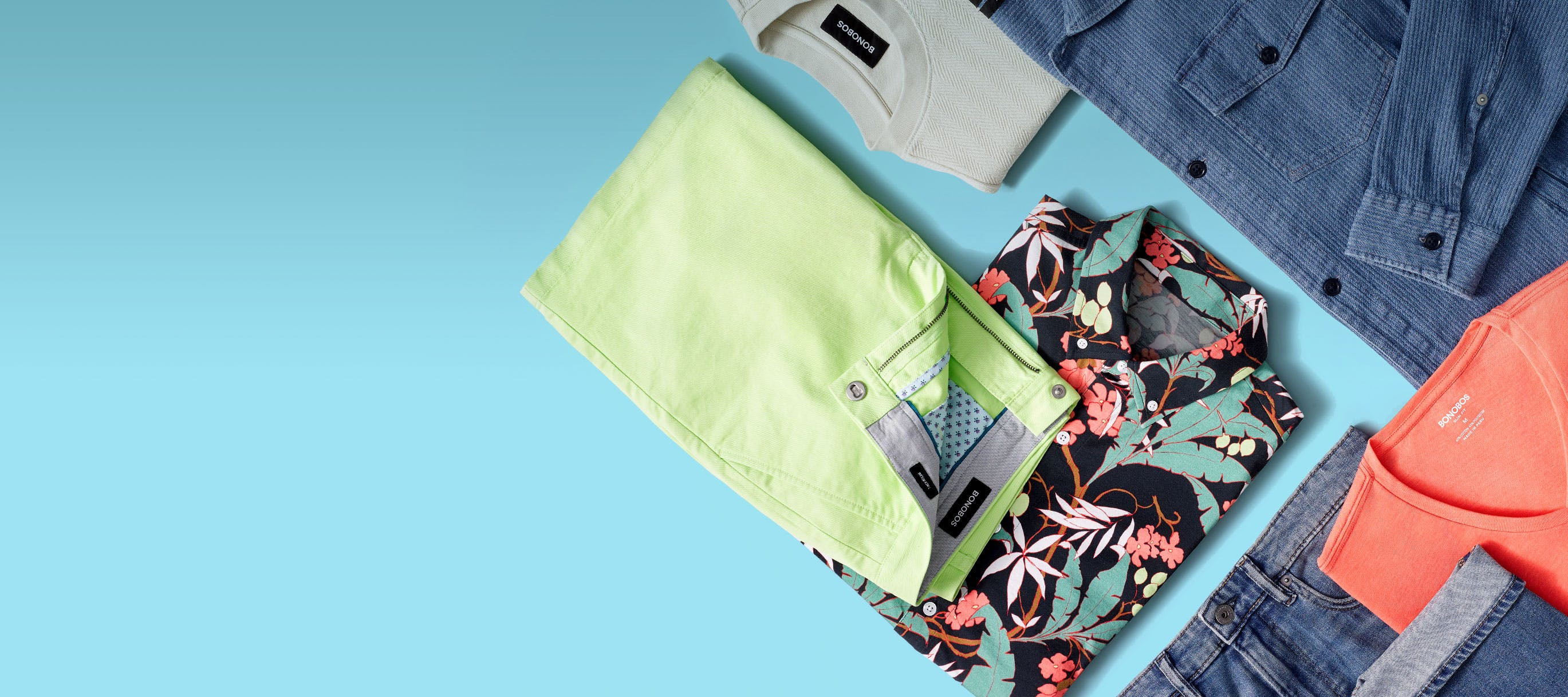 Colorful laydown of clothes on a bright blue background.