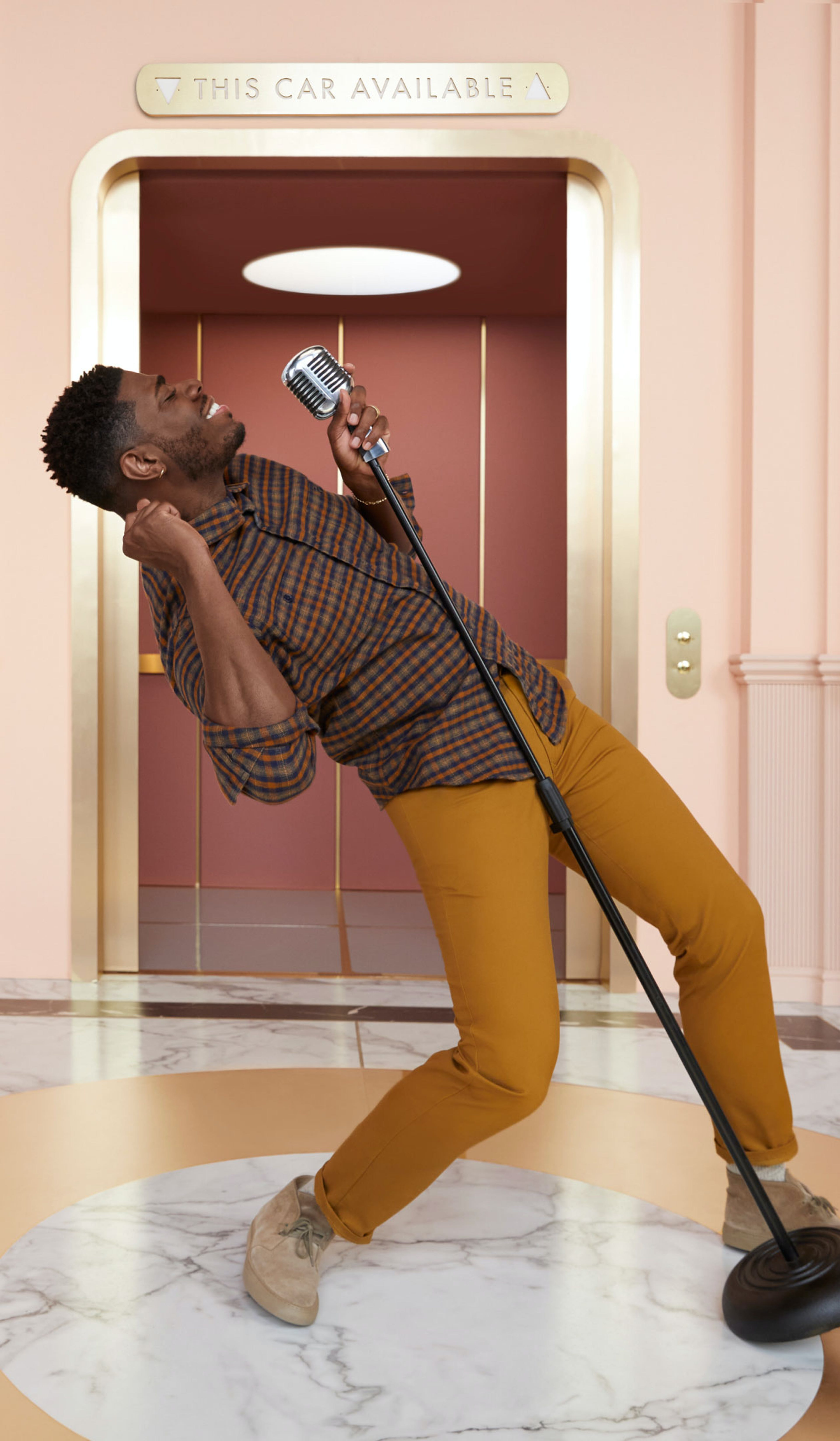Man standing in front of elevator in in sun-yellow chinos, singing with a microphone