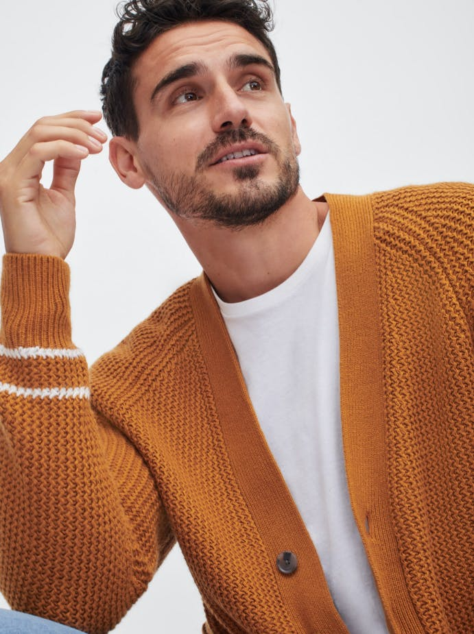 Man wearing an amber color cardigan