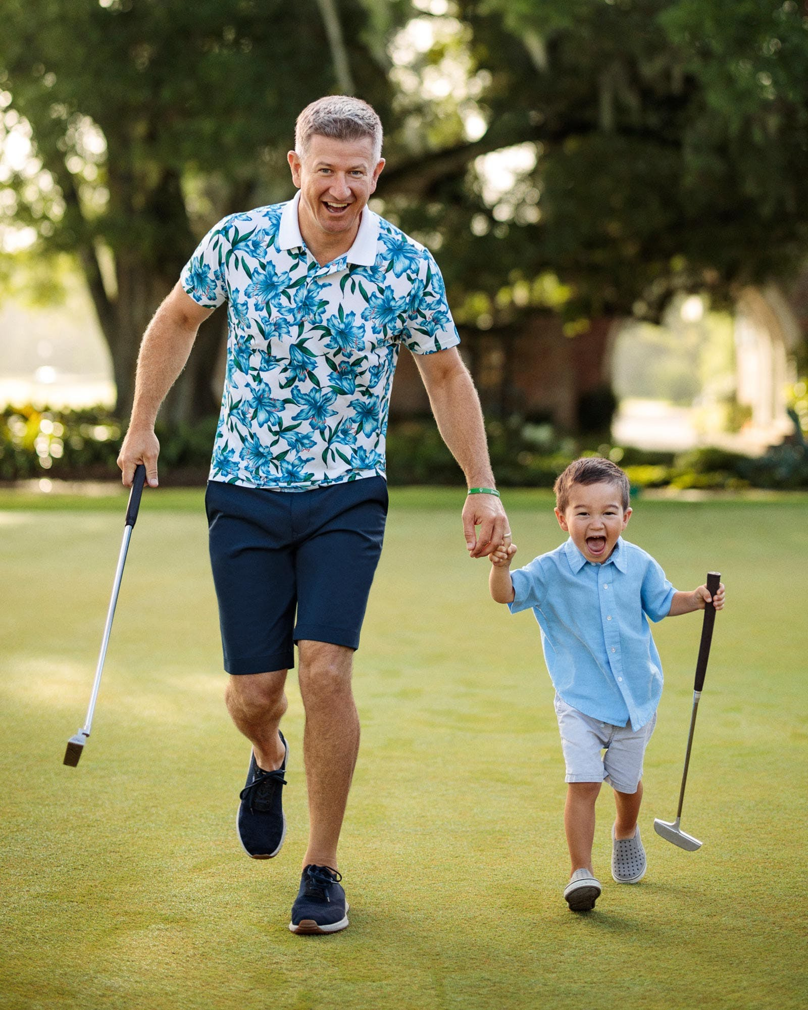 Dad and child holding golf clubs