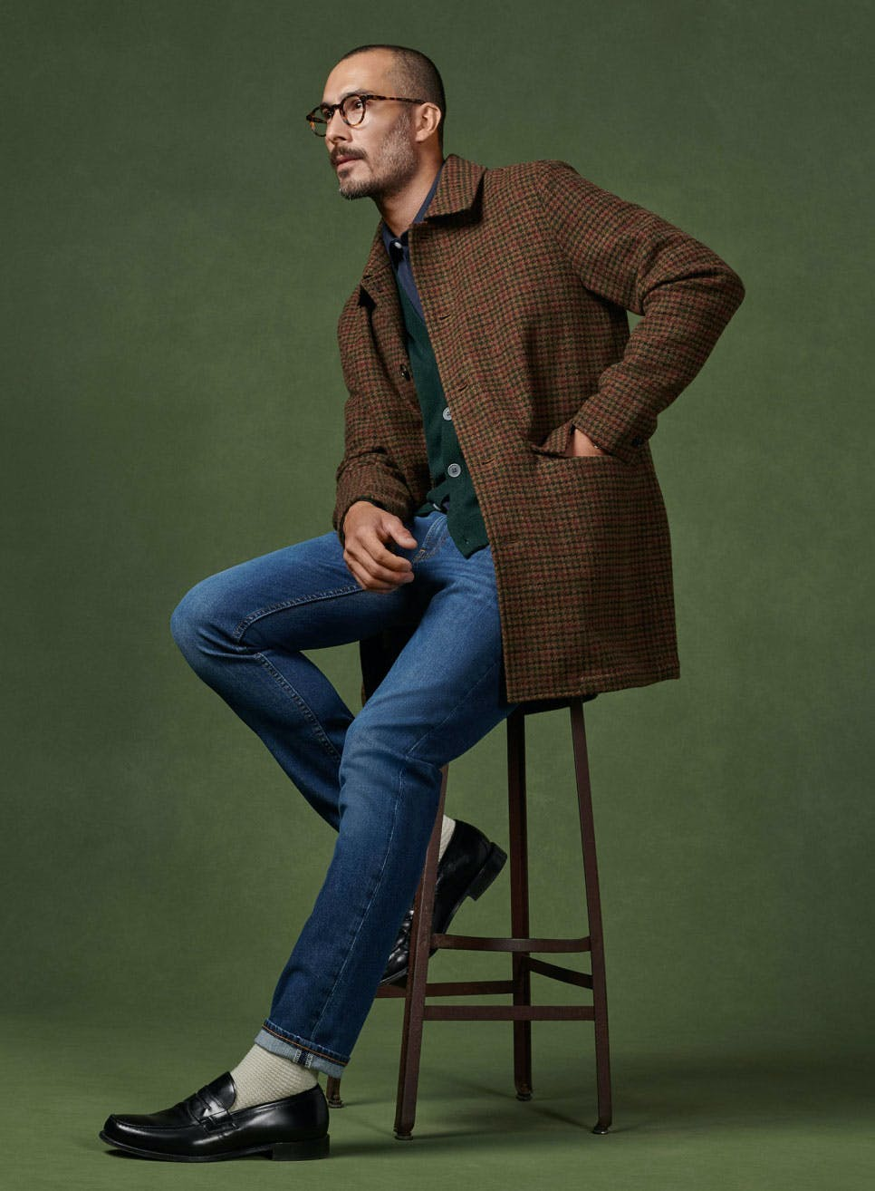 image of man sitting on a stool, wearing all season blue jeans, and brown coat