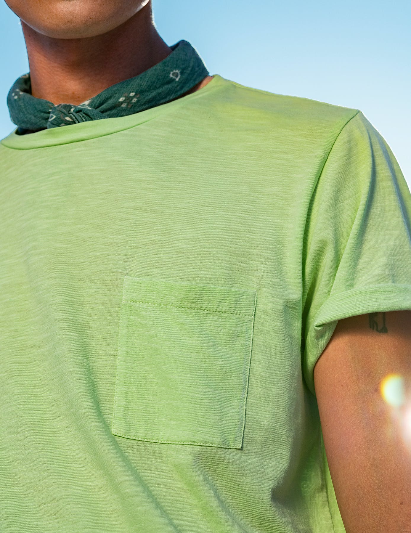 Man wearing green tee shirt and green bandana